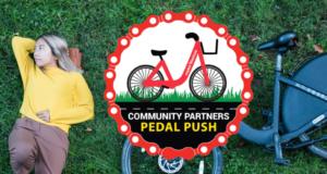 "Woman laying next to bike, says ""Community Partners Peddle Push"""